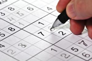 Ein Mann füllt ein Sudoku aus der Zeitung aus